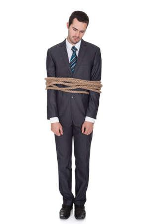 in trouble: Hombre de negocios atado en cuerda. Aislados en blanco