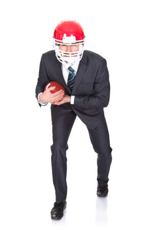 Competitive businessman playing american football. Isolated on white photo