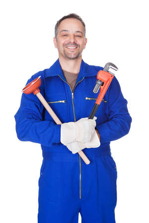 stoppage: Happy Plumber Holding Plunger And Wrench On White Background Stock Photo