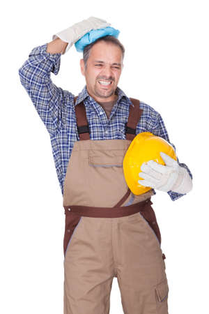 Portrait Of Construction Worker Suffering With Headache On White Background
