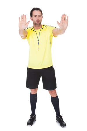 Soccer judge whistling. Isolated on white background photo