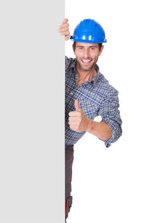 obreros trabajando: Retrato del trabajador feliz presentando bandera vac�a. Aislados en blanco