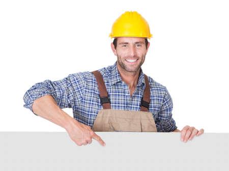 hard worker: Ritratto di felice operaio edile che presenta bandiera vuota. Isolati su bianco