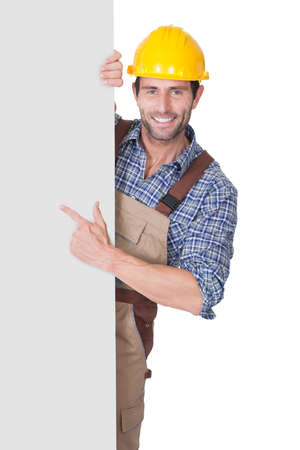 construction sign: Portrait of happy construction worker presenting empty banner. Isolated on white