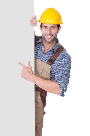 Portret van gelukkige bouwvakker presenteren leeg banner. Geà ¯ soleerd op wit