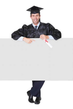 Portrait of happy graduate student presenting empty banner. Isolated on white photo
