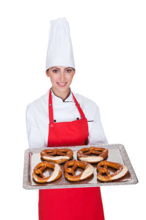 Female Baker Holding Fresh Bavarian Pretzel. Isolated On White photo