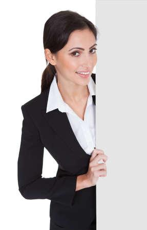 젊은 비즈니스 여자 빈 현수막을 들고 행복 미소입니다. 흰색에 격리