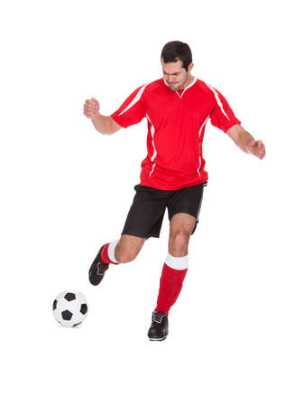 Professional soccer player kicking ball. Isolated on white photo
