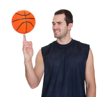 Professional basketball player spinning ball on his finger. Isolated on white photo