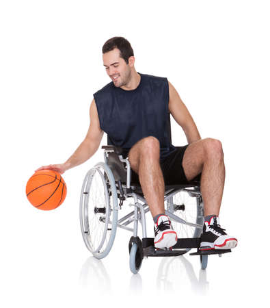 Man in wheelchair playing basketball. Isolated on white photo