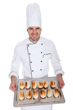 baking tray: Portrait of happy bakerman with tray full of fresh bread. Isolated on white
