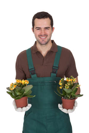 Happy young gardener holding flowers. Isolated on white photo