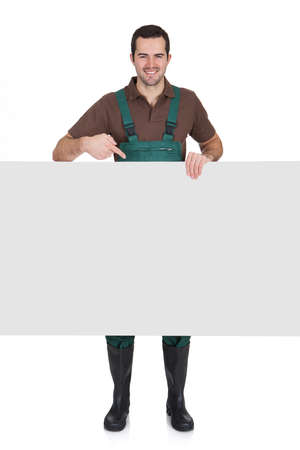 young farmer: Happy young gardener presenting empty banner. Isolated on white Stock Photo