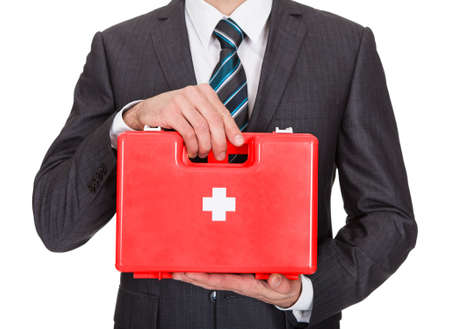 safety first: Happy Businesswoman Holding First Aid Box. Isolated On White Stock Photo
