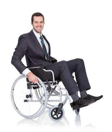 Jeune homme d'affaires dans un fauteuil roulant. Isolé sur fond blanc