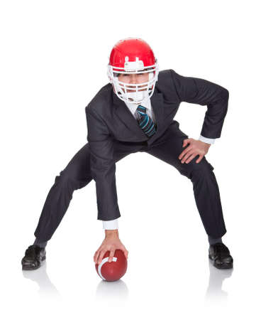 jugando al futbol: Hombre de negocios competitivo jugando al f�tbol americano. Aislados en blanco