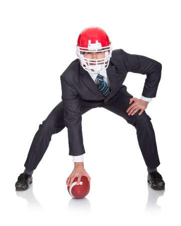 protective helmets: Uomo d'affari competitivo giocare a calcio americano. Isolati su bianco Archivio Fotografico