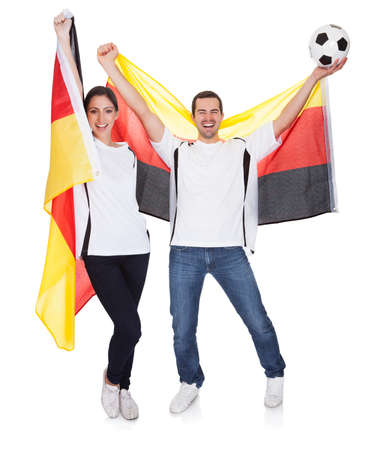 german girl: Young couple cheering for Germany. Isolated on white Stock Photo