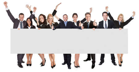 Group of excited business people presenting empty banner. Isolated on white photo
