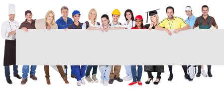 diferentes profesiones: Grupo de profesionales diversos que presentan bandera vacía. Aislados en blanco