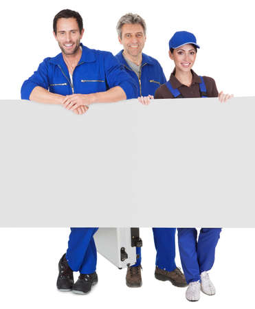 Group of automechanics presenting empty banner. Isolated on white background photo