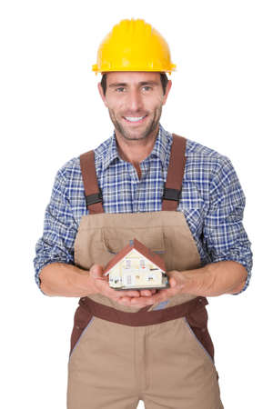 Construction worker presenting house model. Isolated on white photo