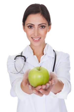 Portrait Of Young Female Doctor Holding Green Apple. Isolated On White photo