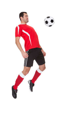 Professional soccer player kicking ball. Isolated on white Stock Photo - 18055595