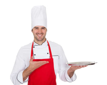 Portrait of cheerful chef presenting empty tray. Isolated on white photo