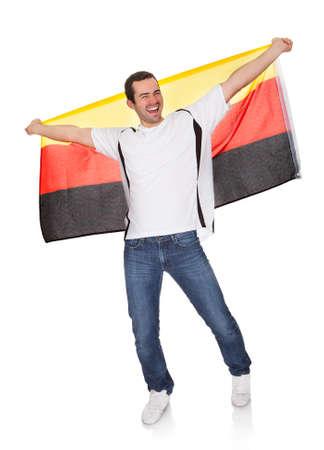 bandera de alemania: Retrato de un hombre feliz sosteniendo una bandera alemana. Aislados en blanco