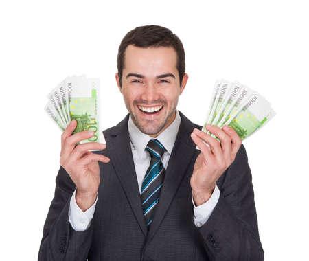 billets euros: Homme d'affaires Excited d�tenant des billets en euros. Isol� sur fond blanc