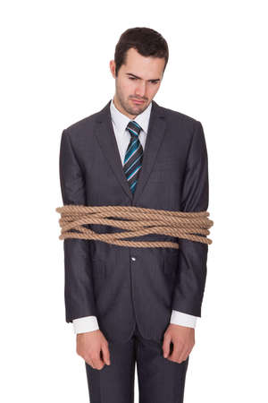man in jail: Businessman tied up in rope. Isolated on white Stock Photo