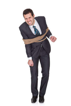 restrained: Businessman tied up in rope. Isolated on white Stock Photo