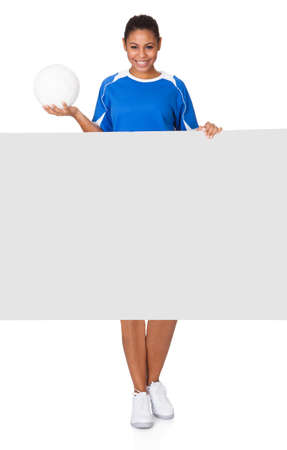 Happy Young Girl Holding Volleyball And Placard. Isolated On White photo
