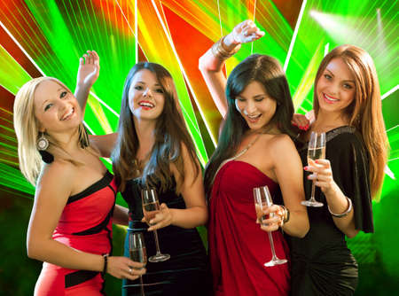 people partying: Group of four stylish women standing in a row toasting with flutes of champagne