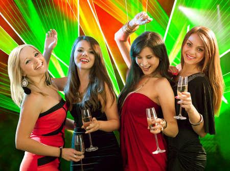 night club: Gruppo di quattro donne alla moda in piedi in una fila brindando con flute di champagne Archivio Fotografico