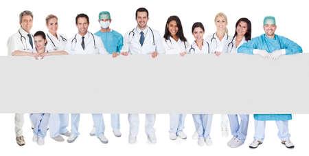빈 배너를 제시하는 의사의 그룹입니다. 흰색에 고립 스톡 콘텐츠