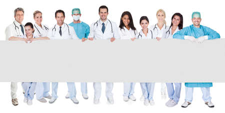 Group of doctors presenting empty banner. Isolated on white photo