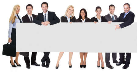 Group of business people presenting empty banner. Isolated on white photo