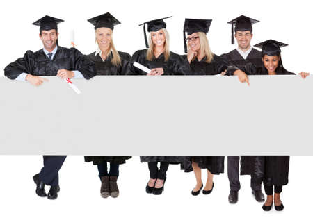 Group of graduate students presenting empty banner. Isolated on white photo