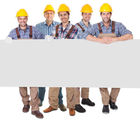 Group of construction workers presenting empty banner. Isolated on white photo