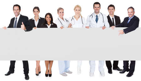 Group of doctors and managers presenting empty banner. Isolated on white photo