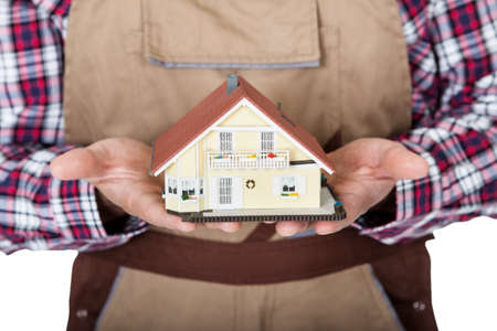 workmen: Construction worker holding house model. Isolated on white background Stock Photo