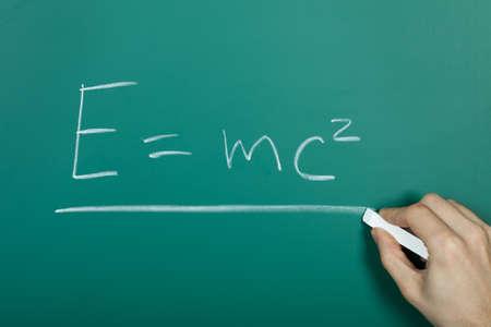 furor: Hand writing relativity formula on green blackboard