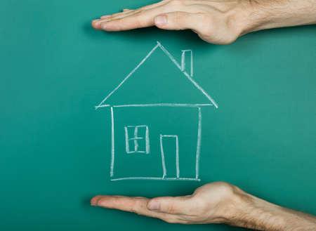 Hand holding chalk drawing house on blackboard photo