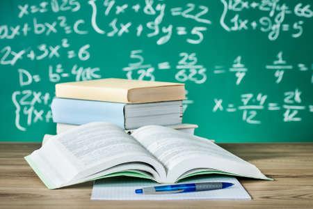 Les manuels scolaires sur un bureau en face du tableau noir Banque d'images