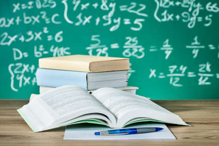 School textbooks on a desk in front of blackboard Stock Photo - 18178551