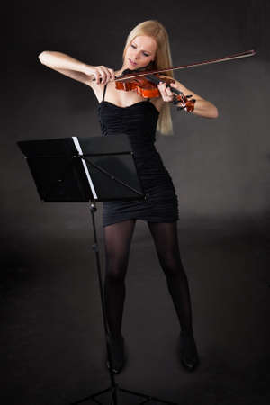 Beautiful young woman playing violin over black background photo