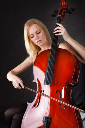 Beautiful young woman playing cello over black background photo